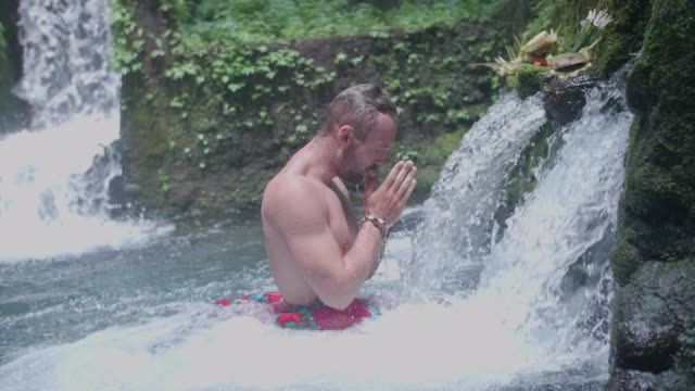 a man washing and praying in a waterfall scenic view in exotic tropical bali, indonesia. - ubud district stock videos & royalty-free footage