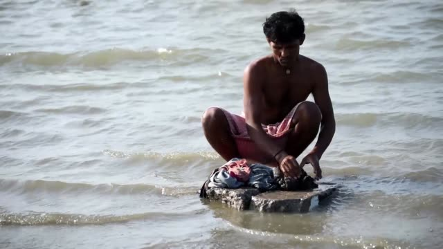 a man washing clothes in the brahmaputra river - india stock videos & royalty-free footage