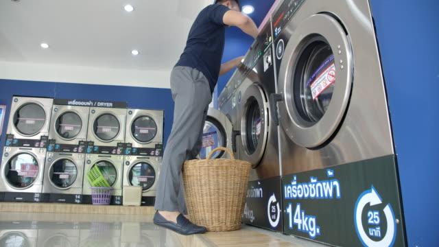 衣類を洗う人 コイン式洗濯機を使う。 - 洗濯かご点の映像素材/bロール