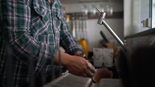 vídeos de stock, filmes e b-roll de homem lavando pratos em casa - lavando louça