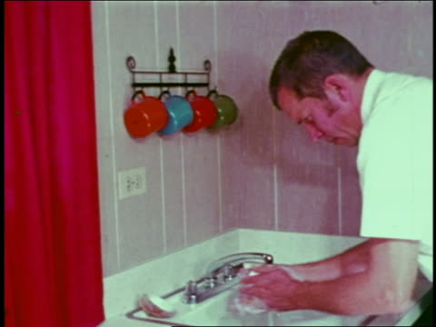 1973 man washing hands with bar of soap at sink - bar点の映像素材/bロール
