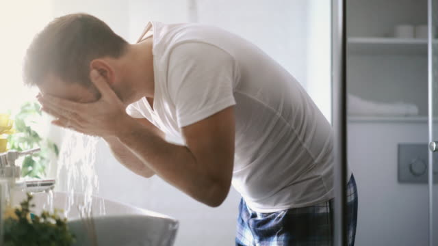 Man washing his face in the morning.
