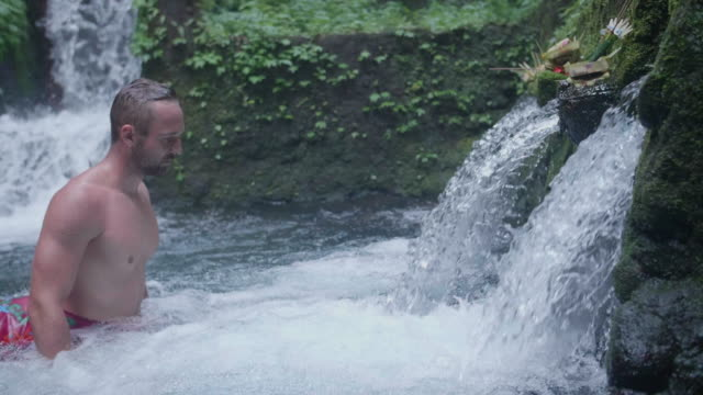 a man washing in a waterfall in exotic tropical bali, indonesia. - ubud district stock videos & royalty-free footage