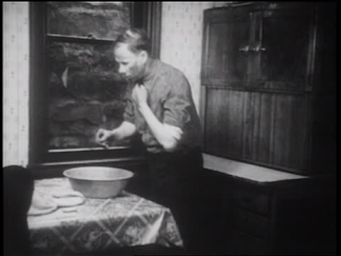 B/W 1939 man washing in basin on table / documentary