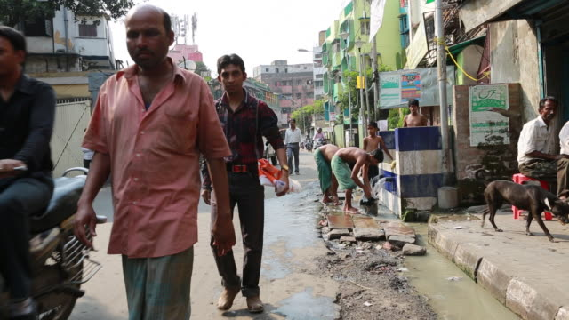 man washing on the street in kolkata (city of joy) - ペディキャブ点の映像素材/bロール