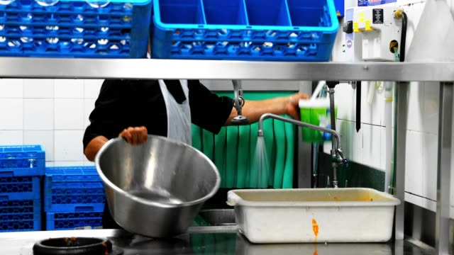 man washing the utensils in a commercial kitchen - washing up stock videos & royalty-free footage