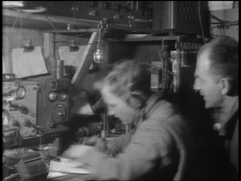 vídeos de stock e filmes b-roll de man watches as radio operator listens on headphones + writes down morse code message - 1920 1929