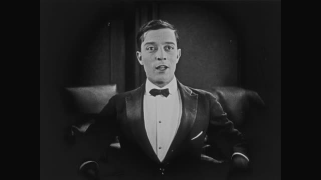1920 a man watches bertie (buster keaton) with an inquisitive glare - asking stock videos & royalty-free footage