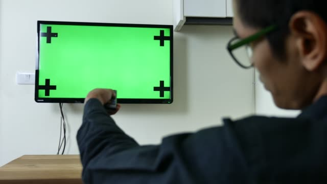 man watches green mock-up screen tv - television chroma key stock videos & royalty-free footage