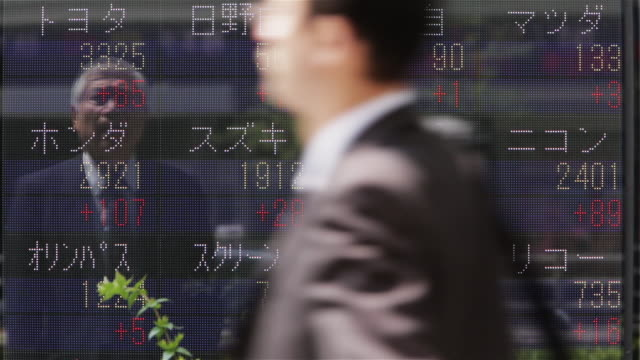 ms a man watches share prices change on a huge display in tokyo's business district / tokyo, japan - 株価点の映像素材/bロール