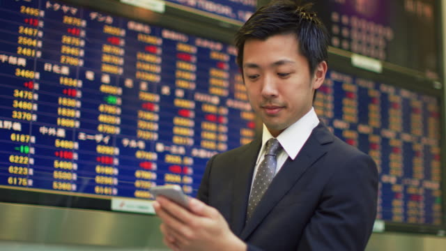 MS A man watches share prices on a screen and looks at his mobile phone / Tokyo, Japan