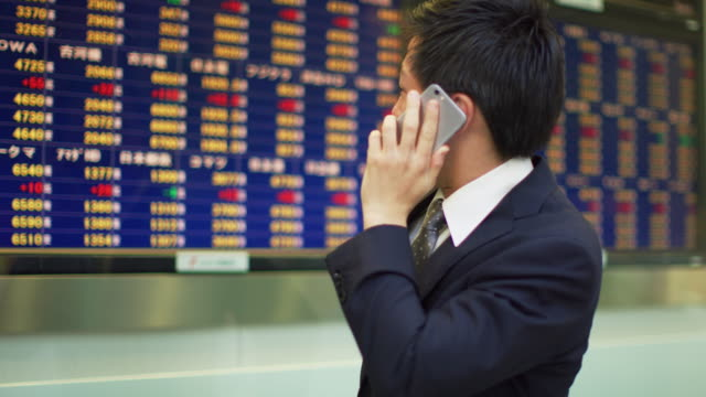 ms a man watches share prices on a screen and talks on a mobile phone  / tokyo, japan - 株価点の映像素材/bロール
