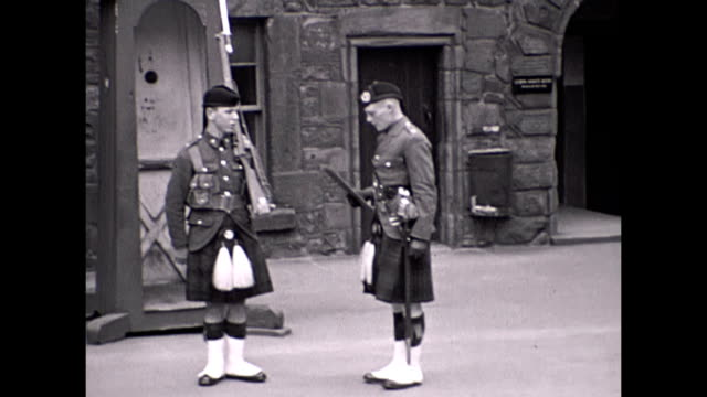 man watches soldiers walk up to the castle, which was still in military use at the time. views of soldiers entering the building with old cars parked... - scottish culture bildbanksvideor och videomaterial från bakom kulisserna
