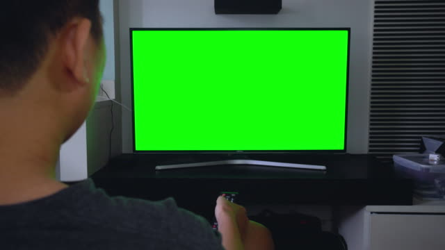 Man watches television green screen on living room