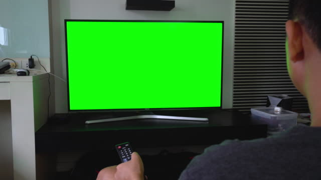 man watches television green screen on living room - television chroma key stock videos & royalty-free footage