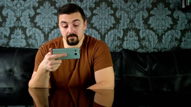 Man watching a video or movie on his smart phone