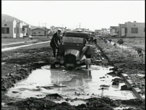 b/w 1924 man (charley chase) watching as car is pushed into large puddle + sinks / feature - mud stock videos & royalty-free footage