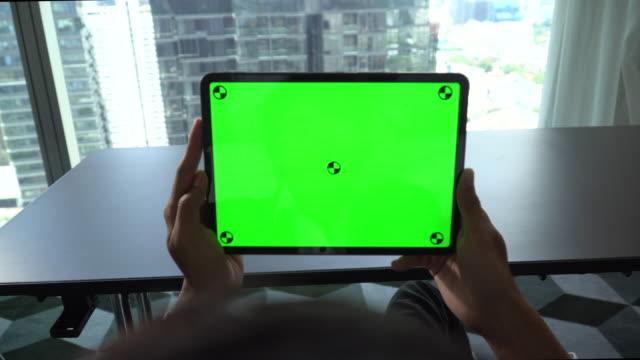 mann beobachtet digitale tablet-grün-bildschirm - gerätebildschirm stock-videos und b-roll-filmmaterial