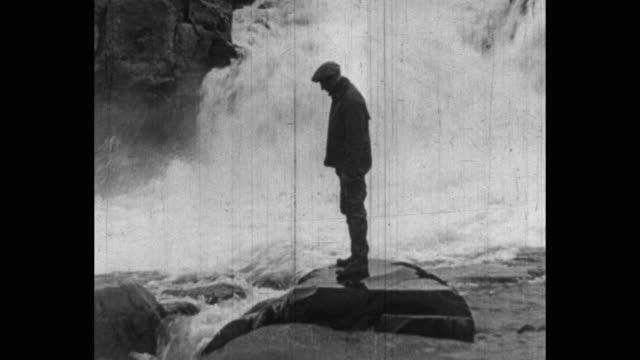 vidéos et rushes de man watching fish jumping in river, fish jumps on rock - chute d'eau