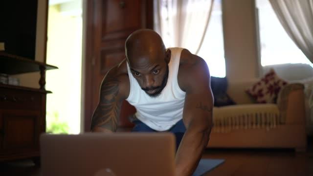 vídeos y material grabado en eventos de stock de hombre viendo la clase de gimnasia en el ordenador portátil y haciendo ejercicios en casa - evento virtual