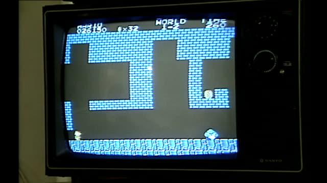 vídeos de stock, filmes e b-roll de man watching mario being played on tv then game over - 1980 1989