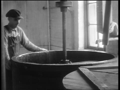 B/W 1932 man watching mechanical mixer spinning in vat / whiskey production / Louisville KY