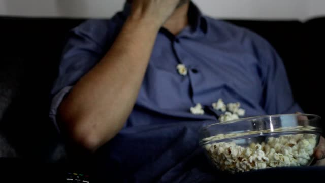 man watching movie and eating fallen popcorn - snack stock videos & royalty-free footage