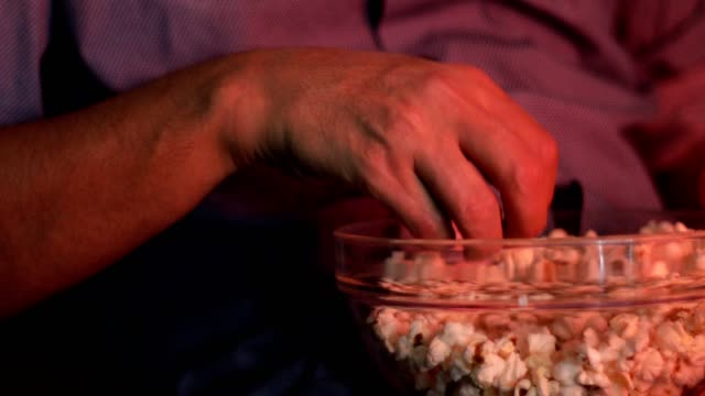 man watching movie and eating popcorn - over eating stock videos & royalty-free footage
