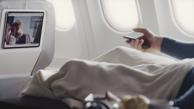 man watching movie in airplane - business travel stock videos & royalty-free footage