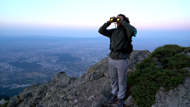 man watching through binoculars the valley below - binoculars stock videos & royalty-free footage