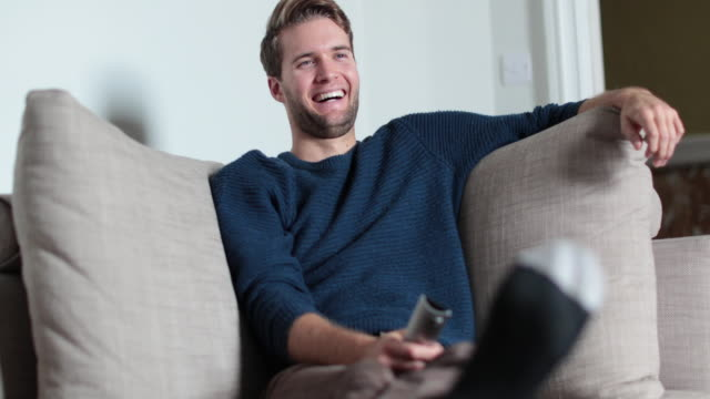 Man watching TV at home on sofa