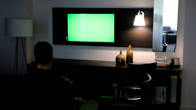 Man watching tv with green screen at hotel room