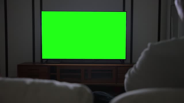 man watching tv with green screen - dark stock videos & royalty-free footage