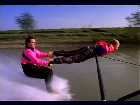 man waterskiing barefoot hanging onto other man's feet - other stock videos & royalty-free footage