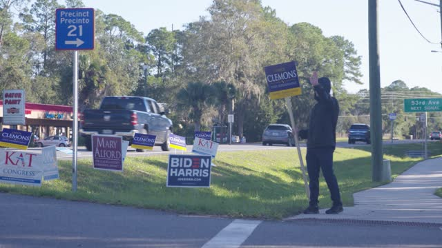 man waves a sign for a candidate on the side of the road as voters enter and leave a precinct as americans go to the polls on u.s. election day on... - enter key stock videos & royalty-free footage