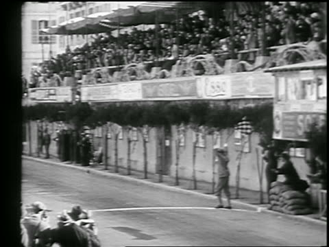 vídeos y material grabado en eventos de stock de man waves checkered flag as car crosses finish line in monaco grand prix / monte carlo - 1933