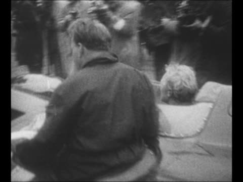 man waves checkered flag as race car crosses finish line at french grand prix race / british flags wave in stands / grand prix winner mike hawthorn... - 1955 bildbanksvideor och videomaterial från bakom kulisserna