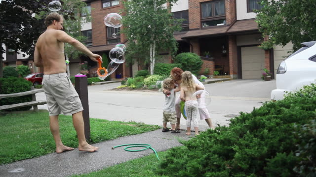 stockvideo's en b-roll-footage met ws man waving around bubble maker in air with two small children on sidewalk /  totonto, ontario, canada - kelly mason videos