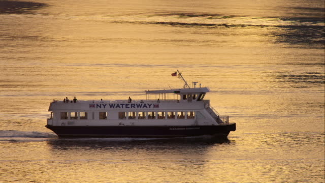 Man waving from ferry moving across Hudson River in slow motion during sunset