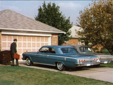 1962 man waving goodbye to wife in car pulling out of driveway / industrial