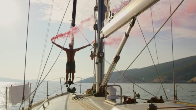 Man waving red distress flare on sailboat, real time