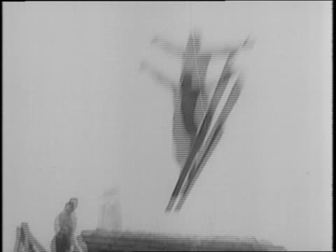 man waxes ski / view of 'norway' written on jacket / man jumps over 'v' for victory symbol / people watching / skier crashes after jumping with two... - 1942年点の映像素材/bロール