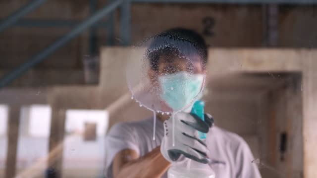 man wear gloves and use antiseptic for cleaning and disinfect covid-19 virus inside the working area - bannister stock videos & royalty-free footage