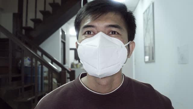 vídeos y material grabado en eventos de stock de hombre usa máscara médica a través de una conferencia telefónica frente a las redes sociales en casa - epidemiología