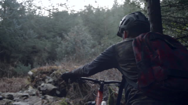 A man wearing a backpack goes mountain biking in the woods. - Super Slow Motion - filmed at 240 fps
