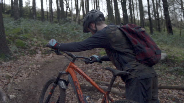 A man wearing a backpack goes mountain biking in the woods.