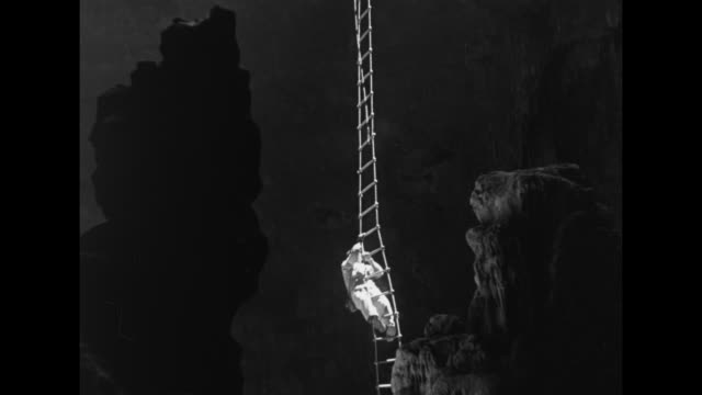 man wearing a baseball cap, white overalls, and protective booties climbs down a very long, precarious, sunlit ladder hanging from the mouth of the... - baseball cap stock videos & royalty-free footage