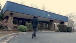 Man wearing a black winter pea coat walking into a generic commercial building