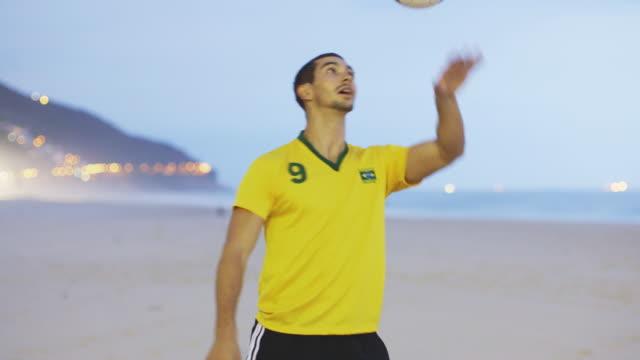 vídeos y material grabado en eventos de stock de ws a man wearing a brazil t-shirt practices his football skills on the beach / rio de janeiro, brazil - perilla