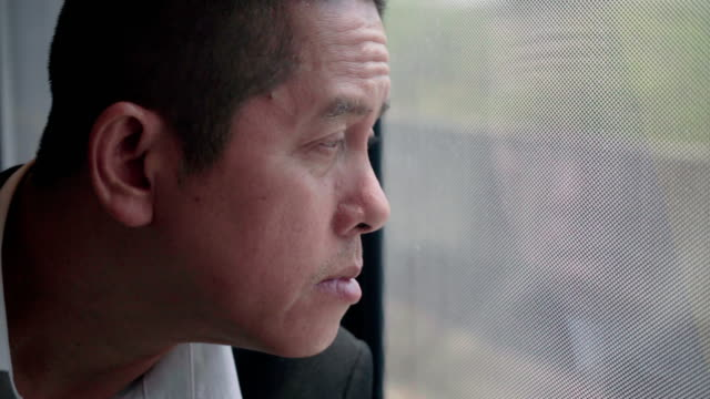 man wearing a business suit gestures weary look on view outside the window of skytrain or subway for travel in the city, ,lifestyle and transportation concept - sad old asian man stock videos & royalty-free footage
